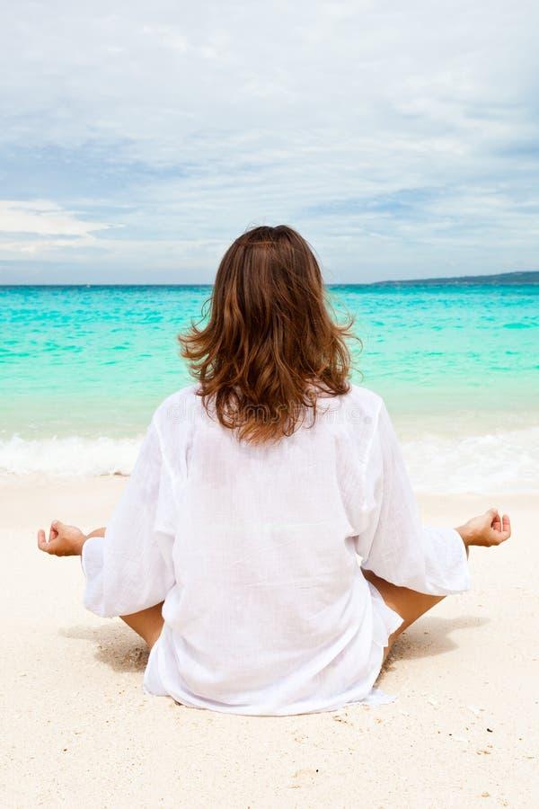 Frau, die auf Strand meditiert lizenzfreie stockfotografie