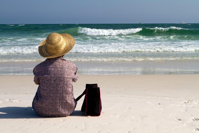 Frau, die auf Strand mit Beutel sitzt lizenzfreie stockbilder