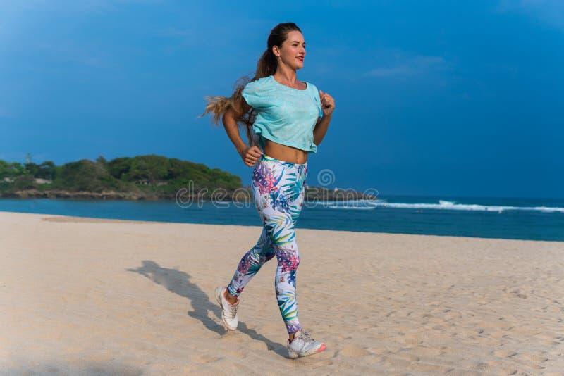 Frau, die auf Strand am Sonnenuntergang läuft Kaukasisches Mädchen der schönen Eignung, das draußen auf Seehintergrund trainiert  stockfoto