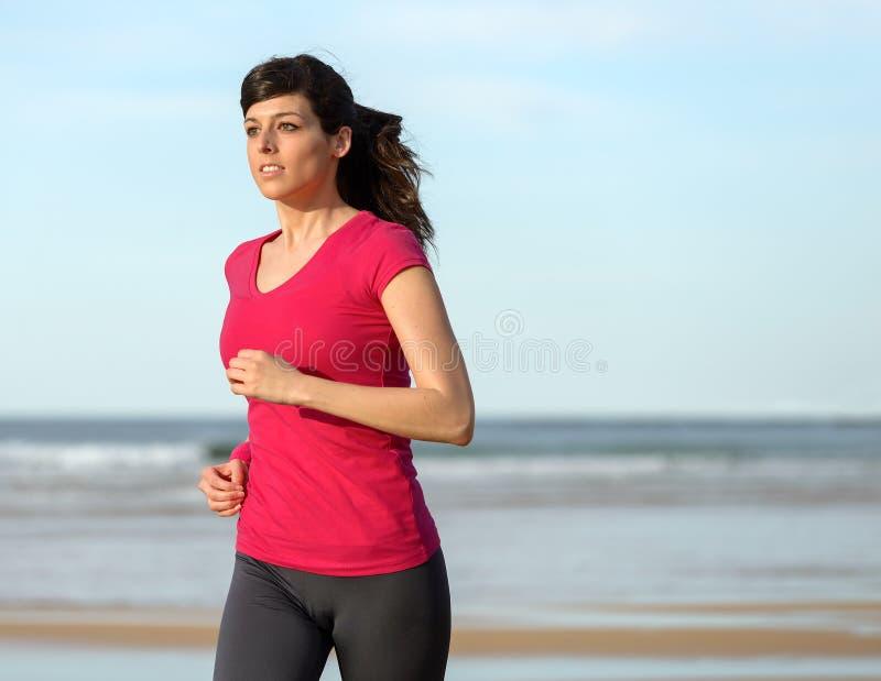Frau, die auf Strand ausarbeitet stockbilder