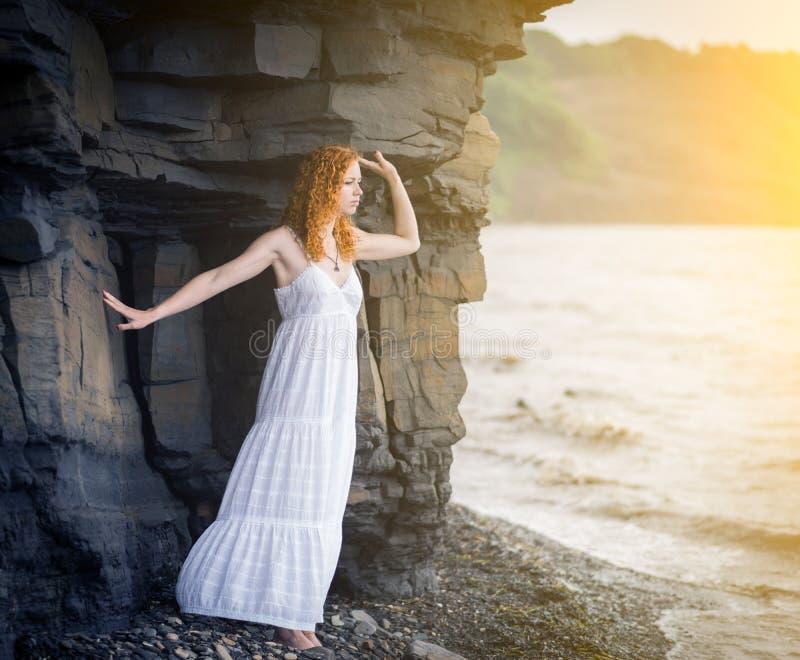 Frau, die auf Strand steht und zum Meer schaut stockbild