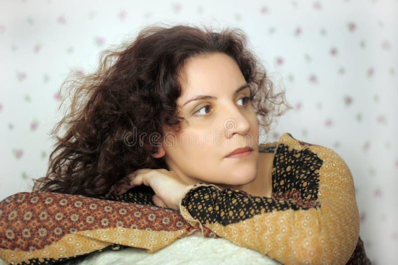 Frau, die auf Stuhl sich lehnt lizenzfreie stockfotografie
