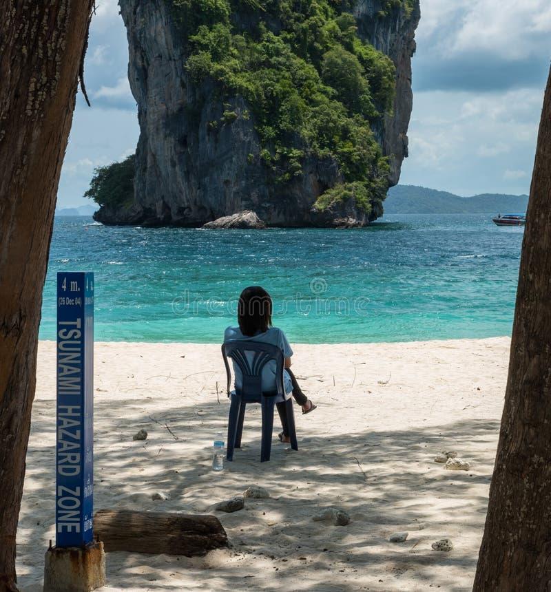 Frau, die auf Stuhl auf Strand sitzt lizenzfreie stockfotos