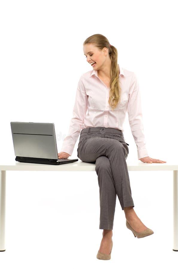 Frau, die auf Tabelle mit Laptop sitzt lizenzfreie stockfotos