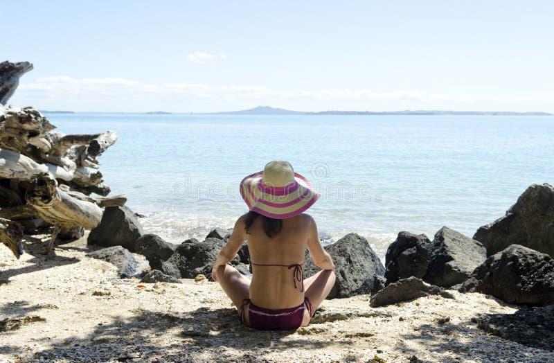 Frau, die auf tragendem Hut des Strandes sitzt stockbilder