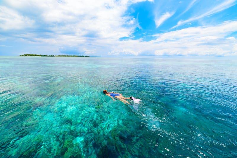 Frau, die auf tropischem karibischem Meer des Korallenriffs, blaues Wasser des Türkises schnorchelt Archipel Indonesiens Wakatobi stockfotos