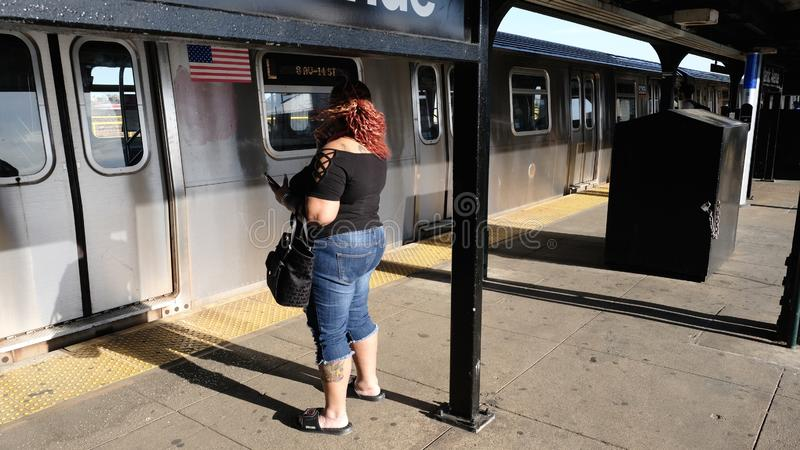 Frau, die auf U-Bahn, Brooklyn, NYC wartet lizenzfreies stockfoto