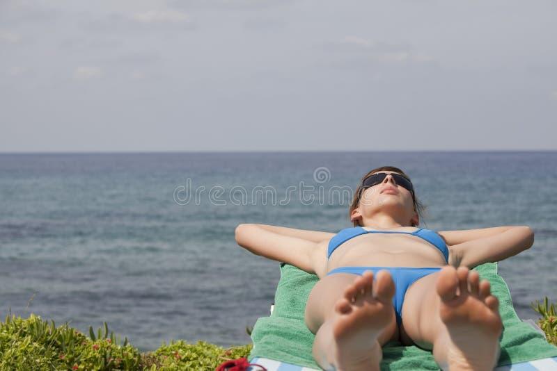 Frau, die auf Wagen ein Sonnenbad nimmt lizenzfreies stockbild