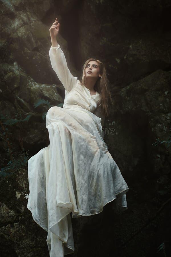 Frau, die auf Waldfelsen aufwirft stockfotos