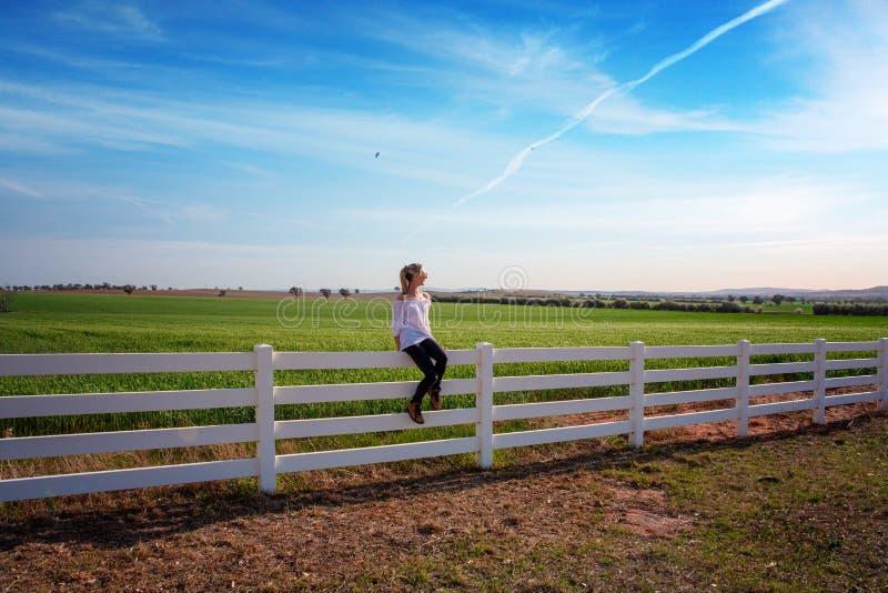 Frau, die auf weißem Bauernhofzaun auf den ländlichen Gebieten sitzt stockbild