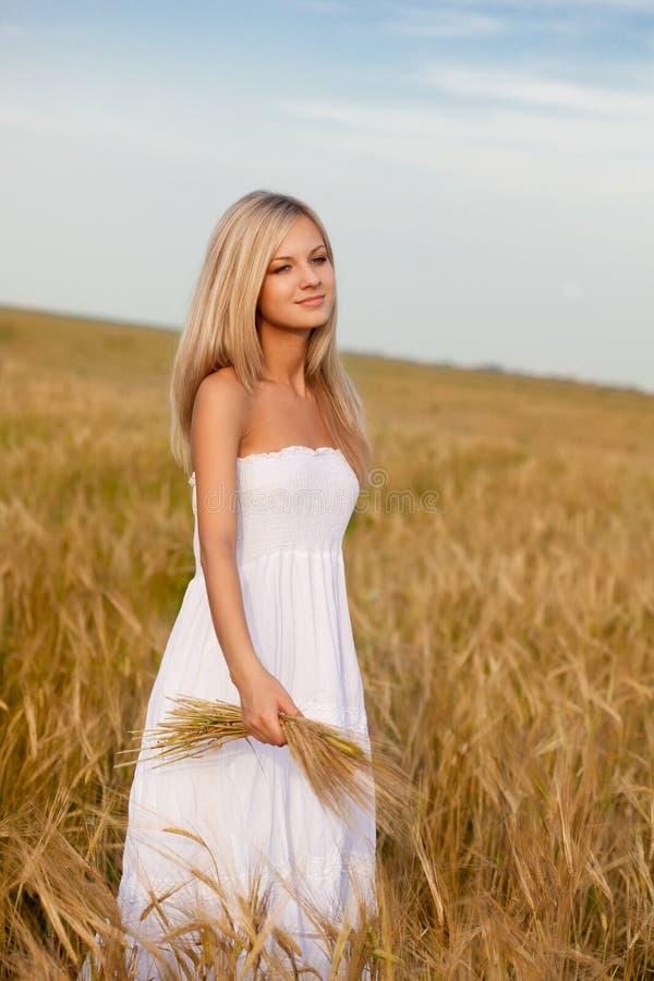 Frau, die auf Weizenfeld geht stockfotos