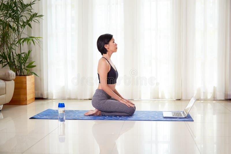 Frau, die auf Yogamatte meditiert lizenzfreies stockfoto