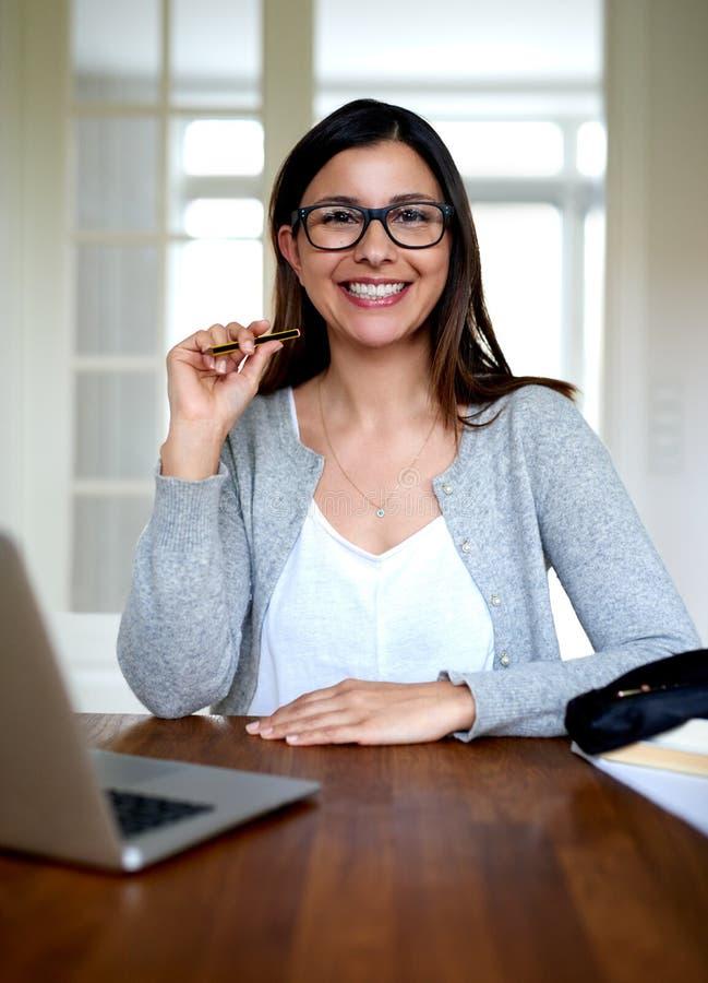 Frau, die aufrecht zu Hause lächeln Schreibtisch sitzt lizenzfreie stockbilder