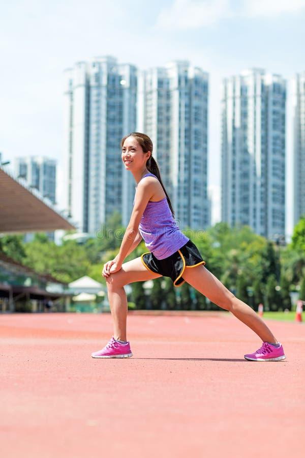 Frau, die Aufwärmenübung im Sportstadion tut lizenzfreies stockbild
