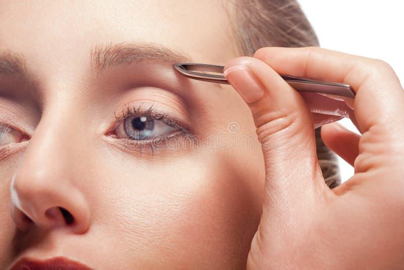 Frau, die Augenbraue zupft stockbild