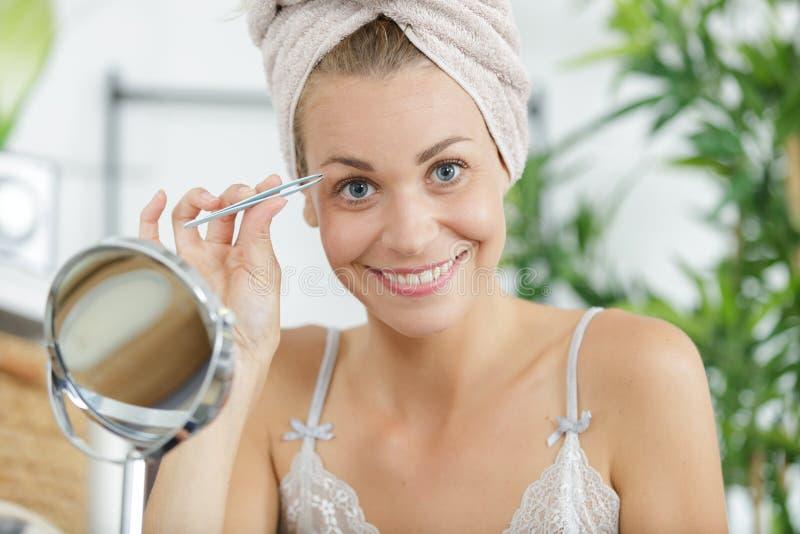 Frau, die Augenbrauen mit Pinzette zupft stockbilder