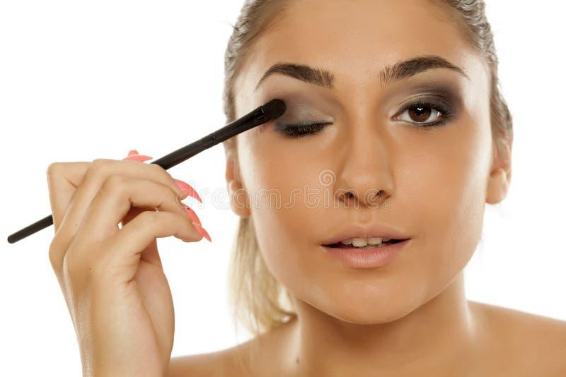 Frau, die Augenschatten anwendet lizenzfreie stockfotografie