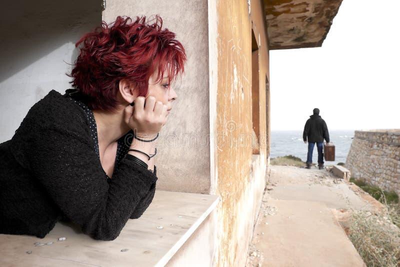 Frau, die aus dem Fenster heraus schaut stockbilder