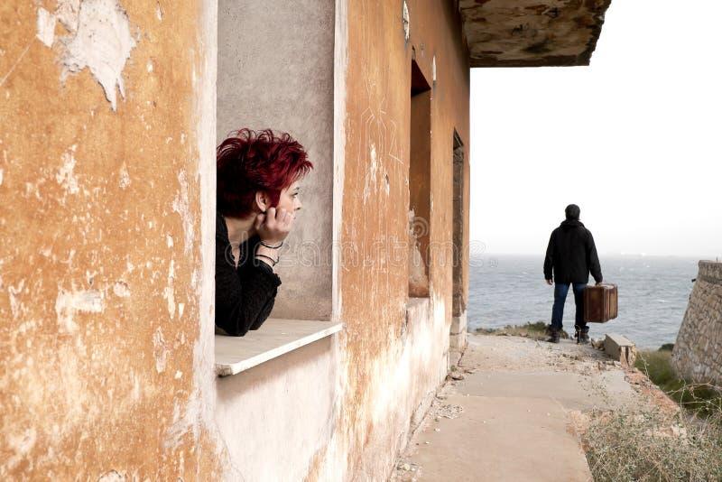 Frau, die aus dem Fenster heraus schaut lizenzfreies stockfoto