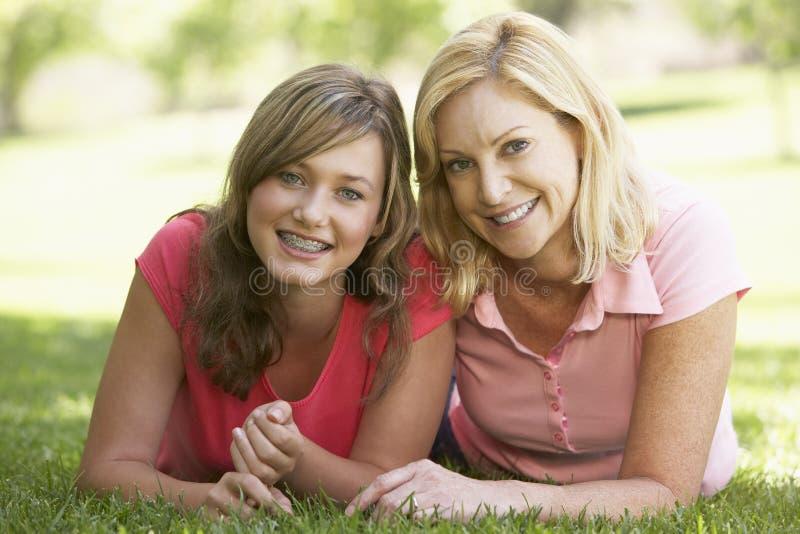 Frau, die aus den Grund mit jugendlicher Tochter liegt stockbild