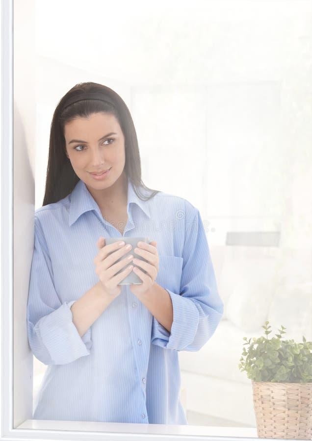 Frau, die aus Fenster mit Kaffee heraus schaut lizenzfreie stockfotos