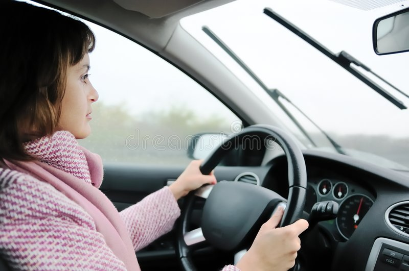 Frau, die Auto im Regen antreibt lizenzfreie stockfotografie
