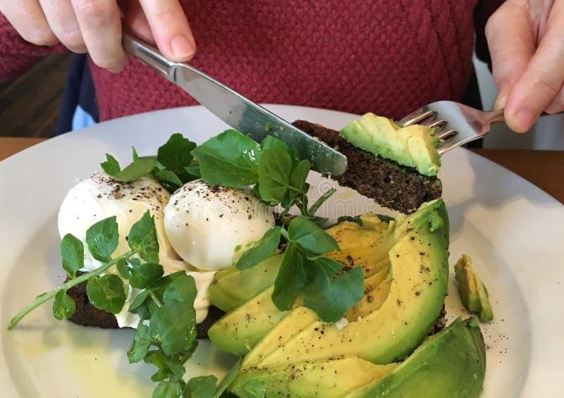 Frau, die Avocado auf Toast für Brunch isst stockfotografie