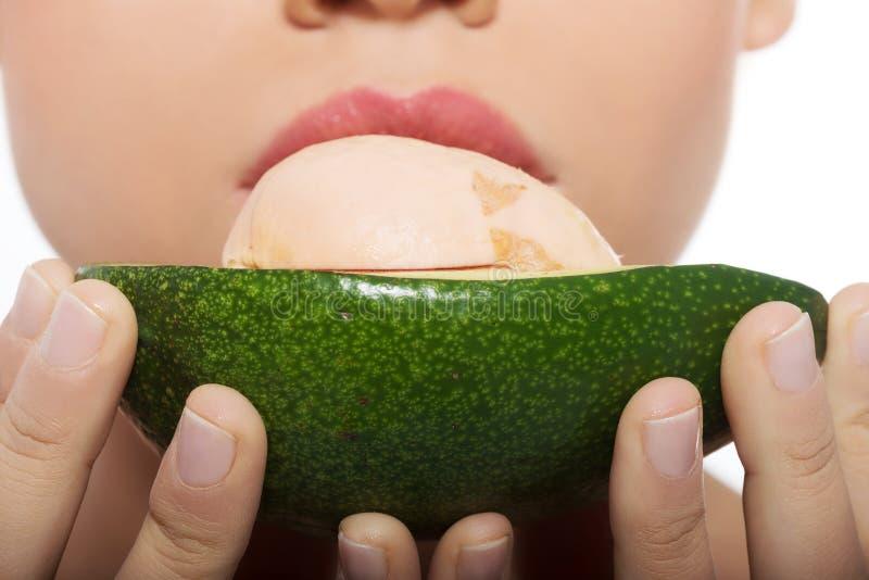 Frau, die Avocado isst lizenzfreie stockfotos