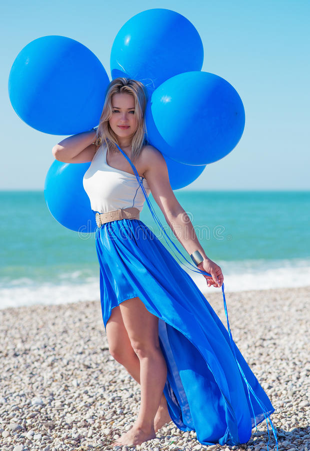 Frau, die Bündel Luftballone am Strand hält stockbild