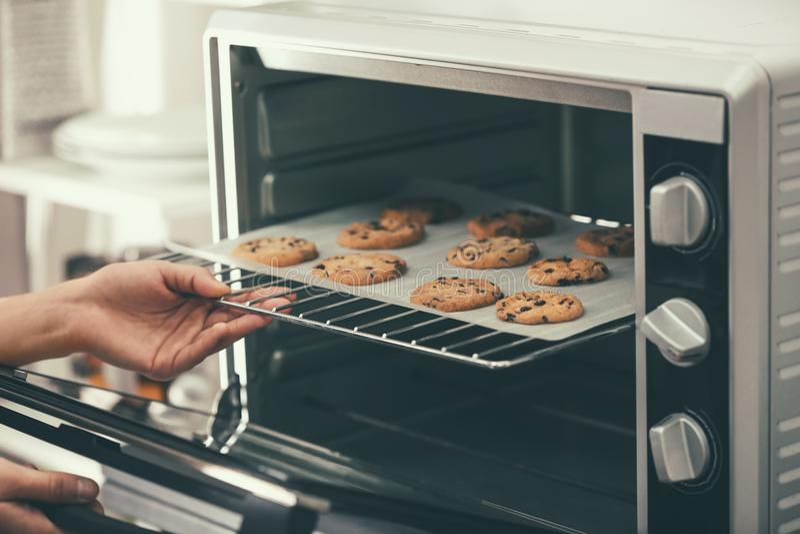 Frau, die Backblech mit Plätzchen vom Ofen herausnimmt, lizenzfreies stockbild