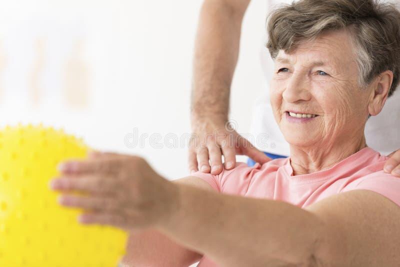 Frau, die Ball in der Physiotherapie hält stockbilder