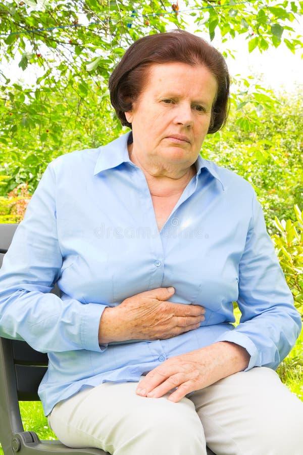 Frau, die Bauchschmerzen, Magen oder Monatsklammern hat stockfotografie