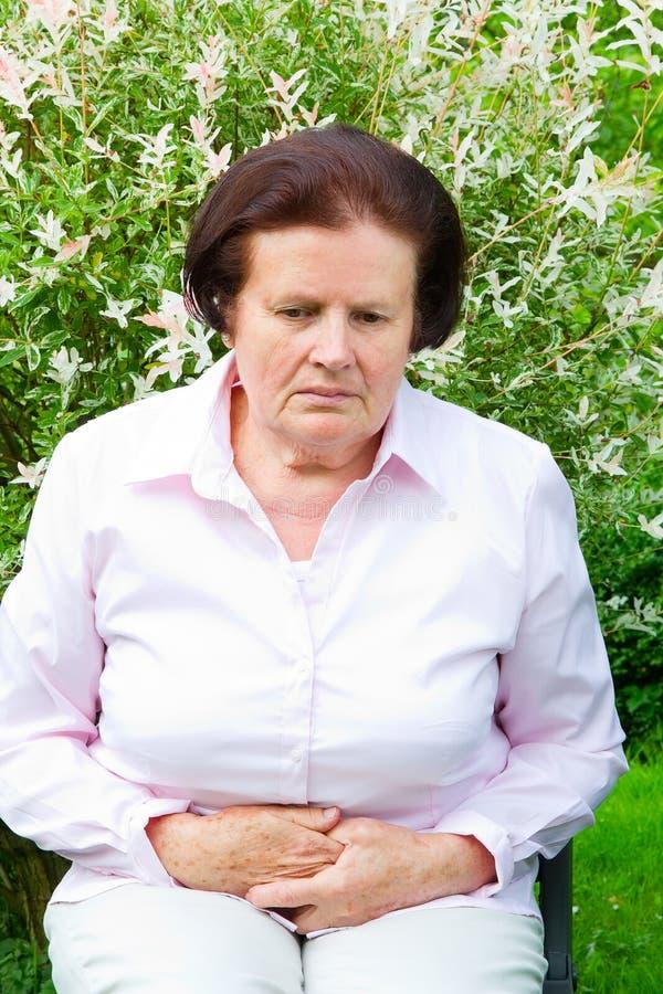 Frau, die Bauchschmerzen, Magen oder Monatsklammern hat lizenzfreies stockfoto