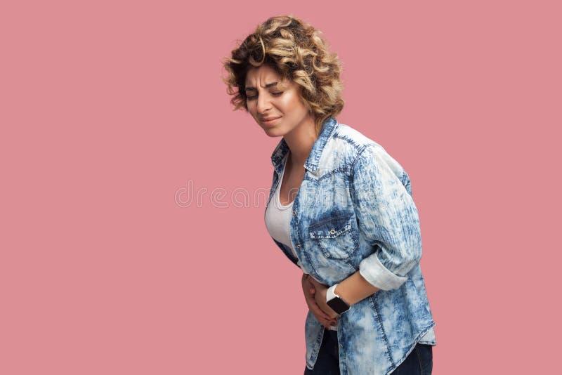 Frau, die Bauchschmerzen, Magen oder Monatsklammern hat Seitenansichtporträt des Profils der umgekippten jungen Frau mit gelockte stockbilder