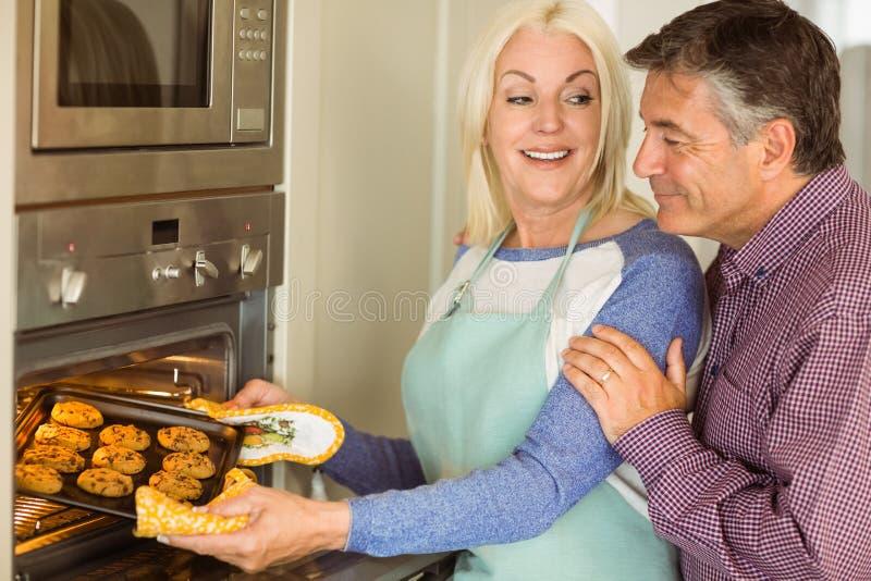 Frau, die Behälter von frischen Plätzchen aus Ofen mit Ehemann heraus nimmt stockfotografie