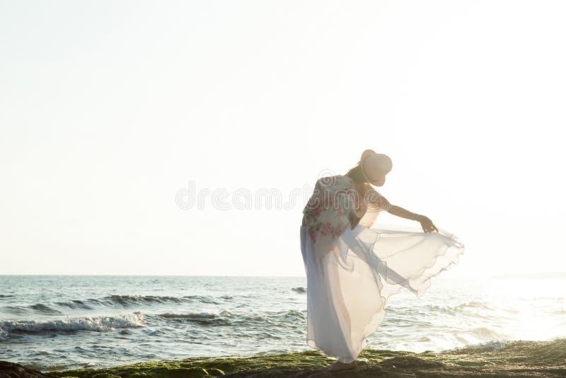 Frau, die bei dem Sonnenuntergang aufwirft stockfotos