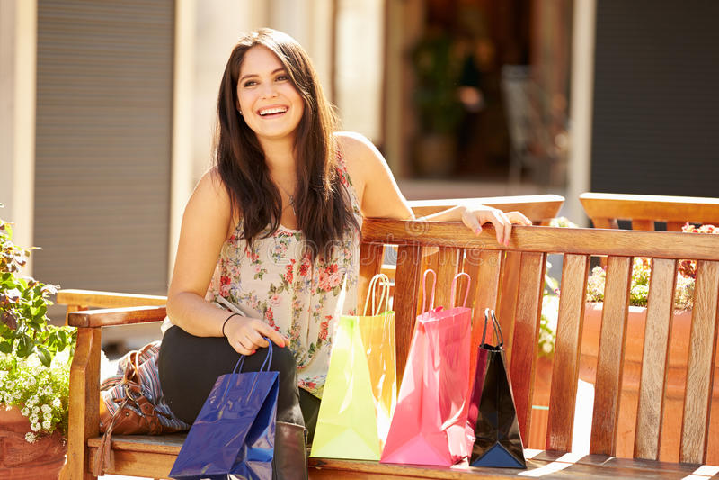 Frau, die bei den Einkaufstaschen sitzen im Mall liegt stockbild
