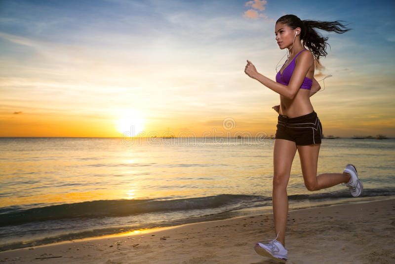 Frau, die bei schönem Sonnenuntergang im Strand läuft lizenzfreies stockfoto