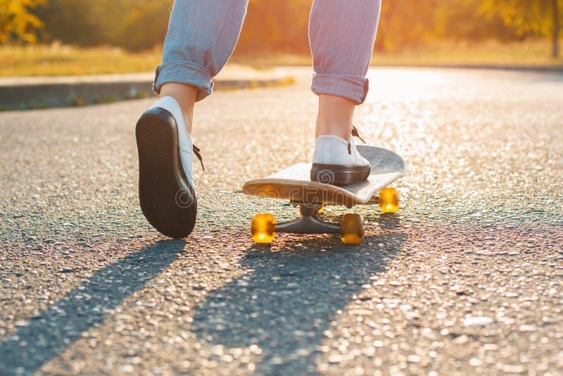 Frau, die bei Sonnenaufgang Skateboard fährt Beine auf dem Skateboard, Bewegungen zu lizenzfreies stockfoto