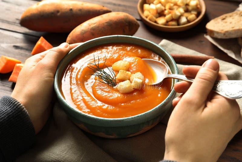 Frau, die bei Tisch geschmackvolle Süßkartoffelsuppe isst lizenzfreies stockfoto