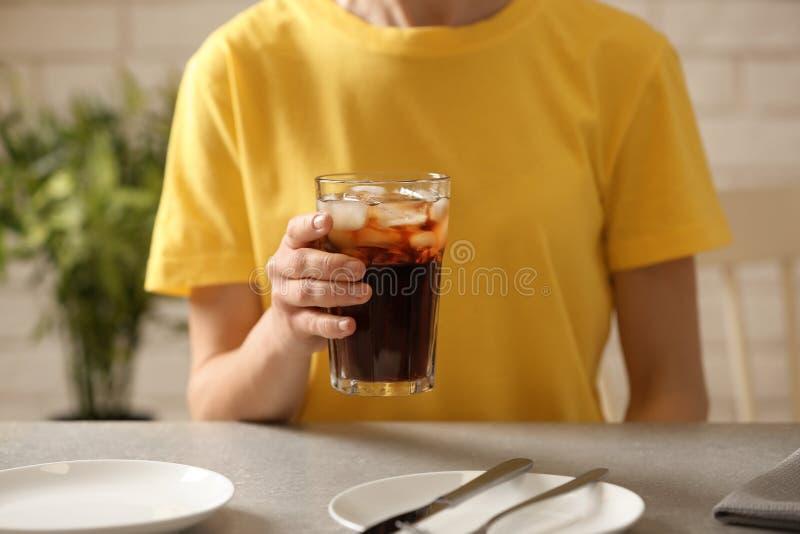 Frau, die bei Tisch Glas Kolabaum mit Eis hält lizenzfreie stockfotografie