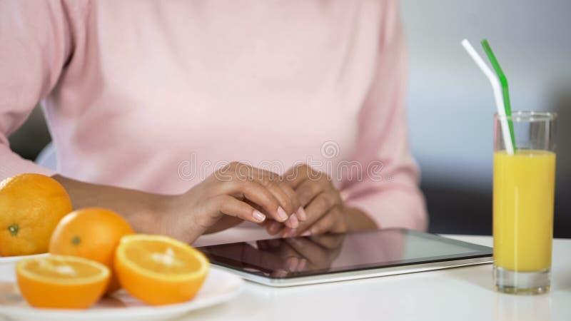 Frau, die bei Tisch Tablette mit den Orangen, suchend nach nahrhafter Diät, Vitamin verwendet stockbild