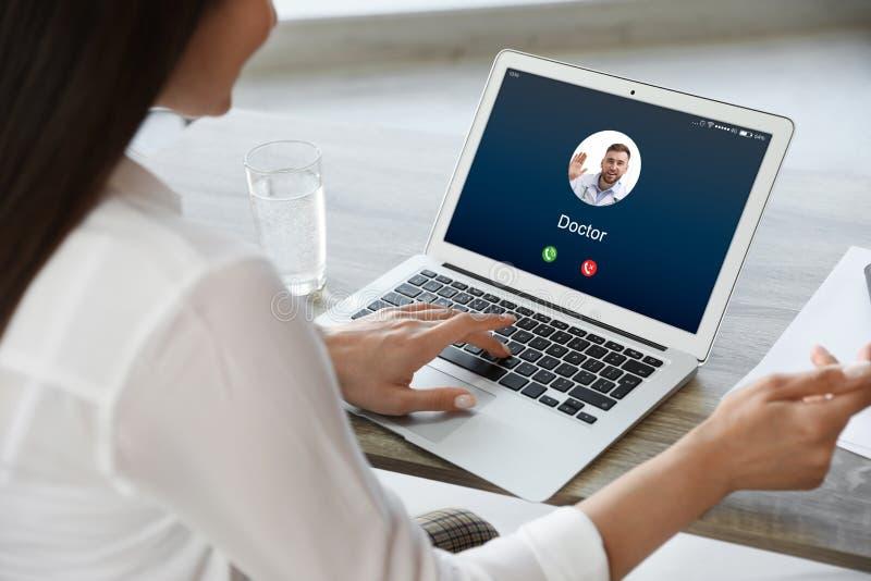 Frau, die bei Tisch Videoanruf von Doktor im Büro empfängt Plaudern zur Welt mithilfe der modernen Technologien lizenzfreie stockfotos