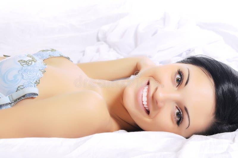Frau, die beim Bettlächeln liegt lizenzfreie stockbilder