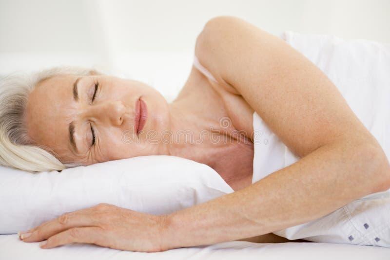 Frau, die beim Bettschlafen liegt lizenzfreie stockfotos