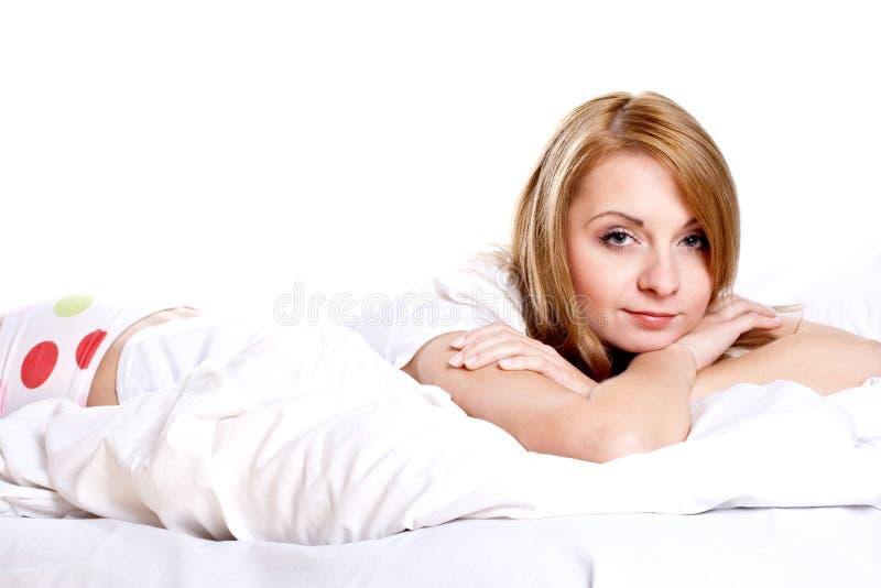 Frau, die beim Schlafzimmerlächeln liegt lizenzfreie stockbilder