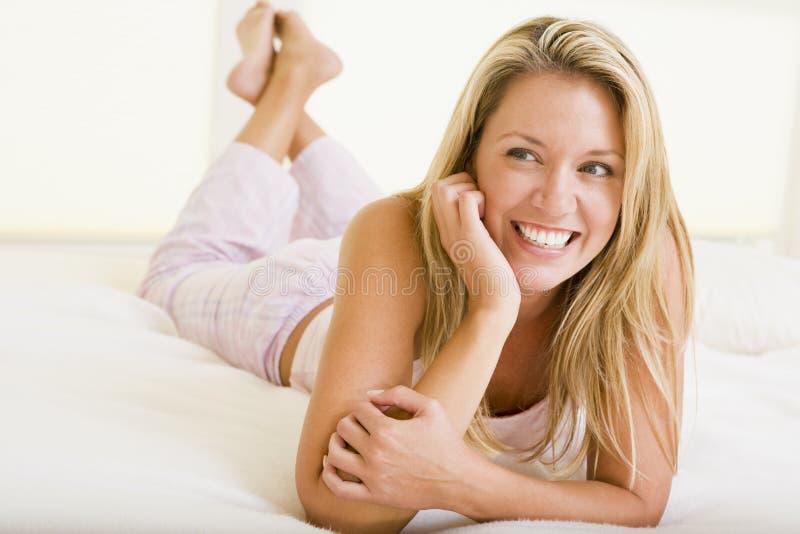 Frau, die beim Schlafzimmerlächeln liegt lizenzfreies stockfoto