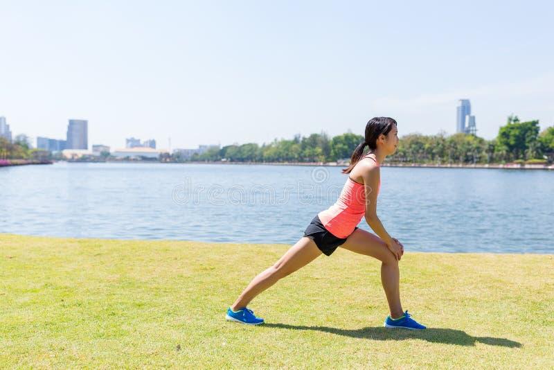 Frau, die Beine bevor dem Laufen ausdehnt lizenzfreie stockbilder