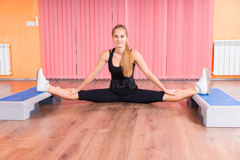 Frau, die Beine mit aeroben Schritt-Plattformen ausdehnt lizenzfreie stockbilder