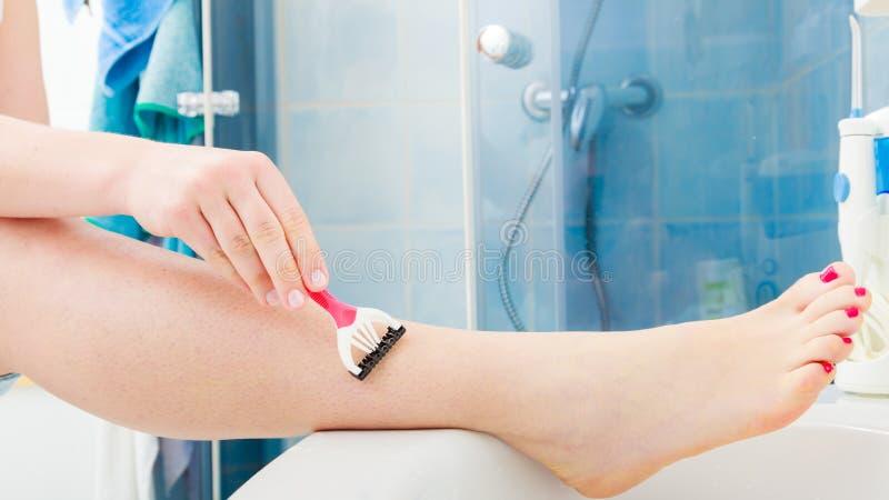 Frau, die Beine mit Rasiermesser im Badezimmer rasiert lizenzfreie stockfotos